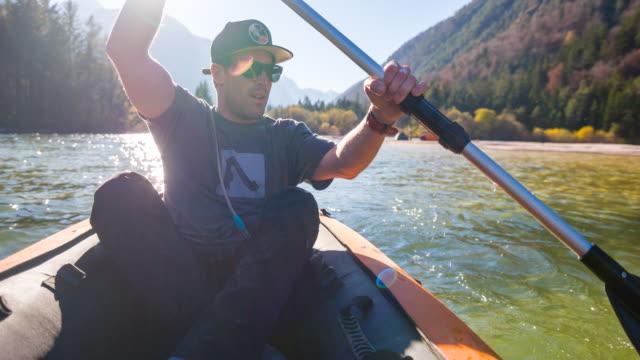 junger mann kanu auf einem see an der bergseite - junger mann allein stock-videos und b-roll-filmmaterial