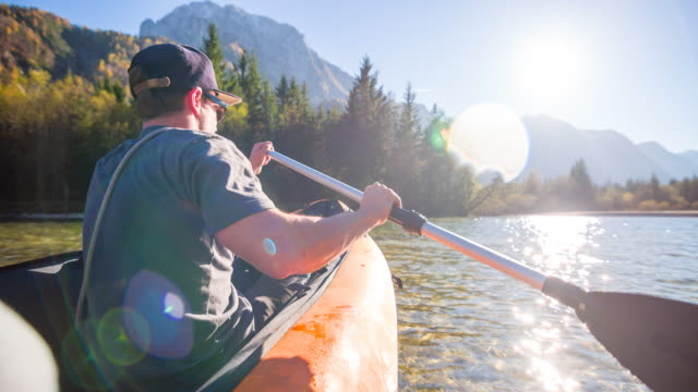 young man canoeing on a lake at the mountainside - canoe stock videos & royalty-free footage