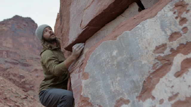 vídeos y material grabado en eventos de stock de young man carefully chooses handholds while free climbing sandstone rock face in moab. - escalada libre