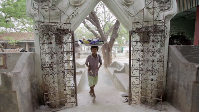 ms young man carrying a basket on top of his head walking through gates of a temple  / mandalay, mandalay division, myanmar - mandalay stock videos and b-roll footage