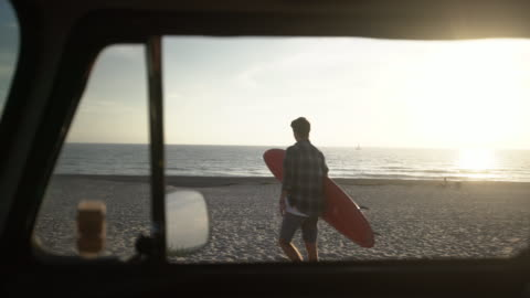 ws young man carrying a surfboard to the beach - surfboard stock videos & royalty-free footage