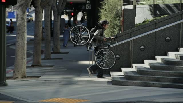 young man carrying bike - 配達員点の映像素材/bロール