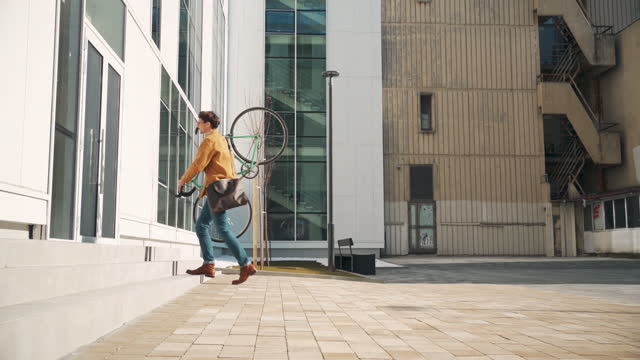 young man carrying his bike on his shoulder while going upstairs - carrying stock videos & royalty-free footage