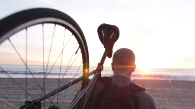 a young man carrying his bike on the beach while watching the sunset over the ocean. - carrying 個影片檔及 b 捲影像