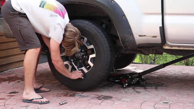 若い男はピックアップトラックの車輪を変更します - 交代点の映像素材/bロール