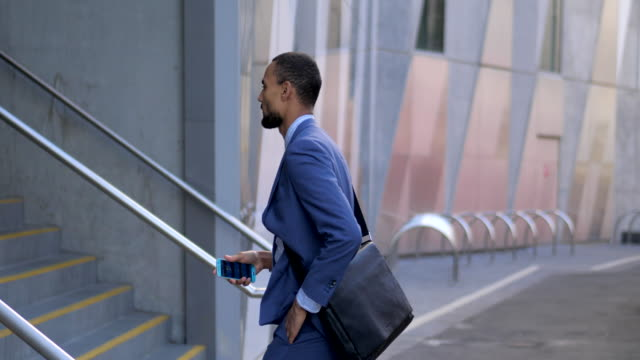 young man checking his mobile phone before walking up the stairs - steps and staircases stock videos & royalty-free footage
