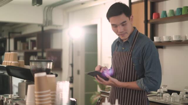 vídeos y material grabado en eventos de stock de joven revisando existencias con tableta digital en su café - lista de chequeo