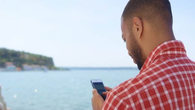 Young man checking the photos he made on his smartphone while standing on a seaside walkway
