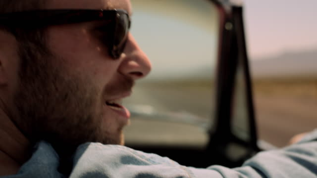 a young man chews a toothpick and smiles over his shoulder as he rides in a convertible down a desert highway. - collector's car stock videos and b-roll footage