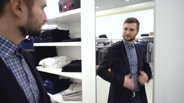 young man chooses for himself new clothes at the mall. - omklädningsrum bildbanksvideor och videomaterial från bakom kulisserna