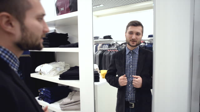 stockvideo's en b-roll-footage met young man chooses for himself new clothes at the mall. - designerkleding
