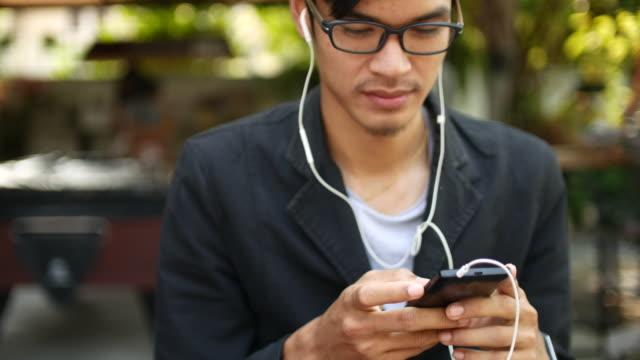 Giovane uomo scegliendo e ascoltando musica su smartphone, 4 k (UHD