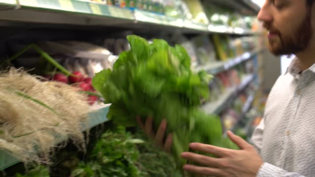 young man choosing fresh vegetables at the supermarket - mixed race person stock videos & royalty-free footage