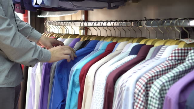 young man choosing shirt in the clothing store - button down shirt stock videos & royalty-free footage
