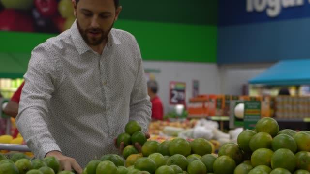 junger mann wählt etwas limette im supermarkt - kunden orientiert stock-videos und b-roll-filmmaterial