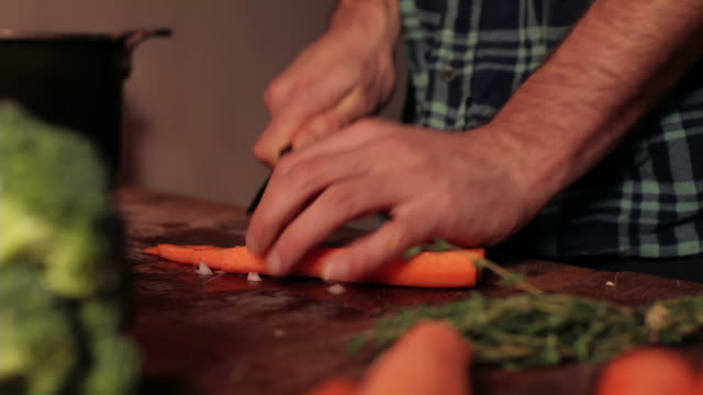 cu young man chopping carrots / kingston, new york, usa  - carrot stock-videos und b-roll-filmmaterial