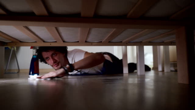 vídeos de stock e filmes b-roll de young man cleaning a floor under a bed lying on the floor - limpar