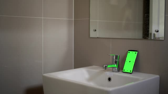 a young man cleans his teeth and looking at  green screen smartphone in the bathroom - bathroom stock videos & royalty-free footage