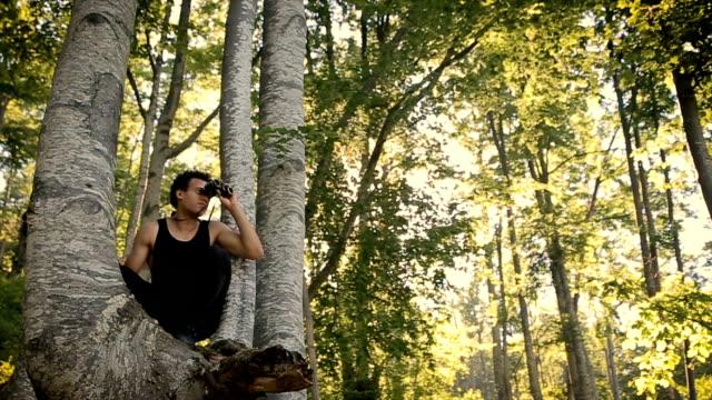Jonge man klimmen op de boom en door de verrekijker kijkt