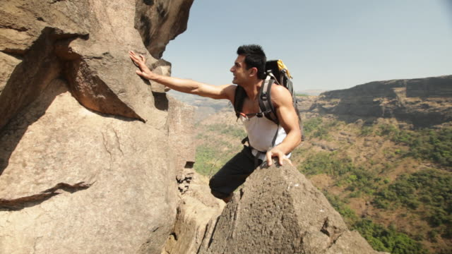 young man climbing a cliff of mountain  - rock climbing stock videos and b-roll footage