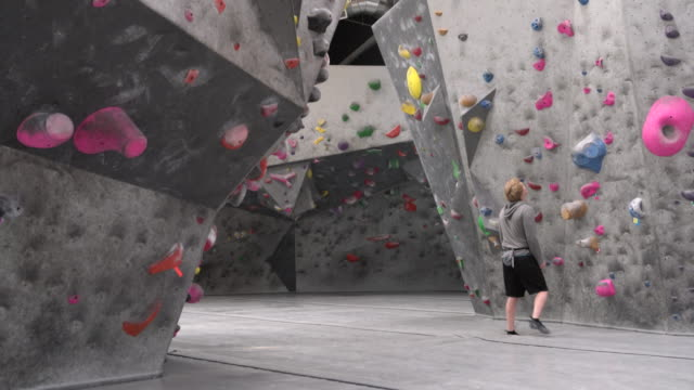 stockvideo's en b-roll-footage met ws young man climbing a rock climbing wall - boulder rock