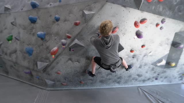 stockvideo's en b-roll-footage met ws ts young man climbing a rock climbing wall - boulder rock