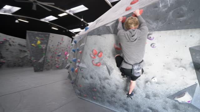 stockvideo's en b-roll-footage met ws ds young man climbing a rock wall - boulder rock