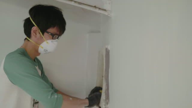 Young man climbing ladder and cleaning exhaust fan inside kitchen room.