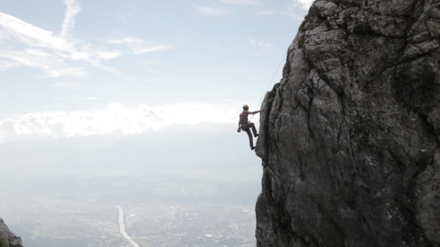 young man climbing up a mountain near a city - rock climbing stock videos & royalty-free footage