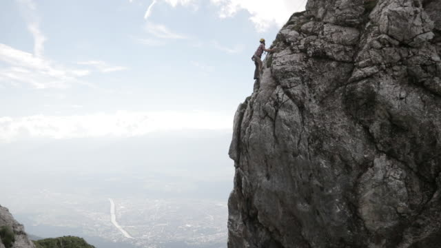 young man climbing up a mountain near a city - felsklettern stock-videos und b-roll-filmmaterial