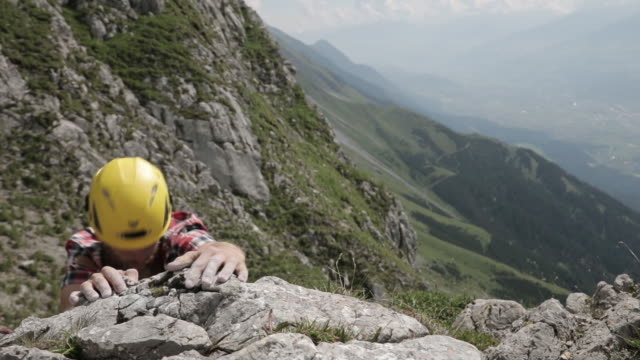 young man climbing up a mountain - top garment stock videos and b-roll footage