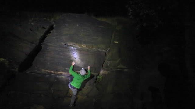 vidéos et rushes de a young man climbs boulders at night while bouldering. - time-lapse - lampe frontale