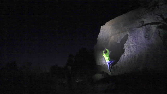 a young man climbs boulders at night while bouldering. - time-lapse - electric torch stock videos & royalty-free footage