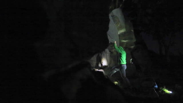 vidéos et rushes de a young man climbs boulders at night while bouldering. - lampe frontale