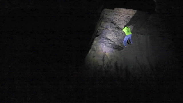 a young man climbs boulders at night while bouldering. - masso video stock e b–roll