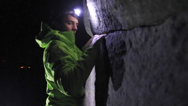 a young man climbs boulders at night while bouldering. - head torch stock videos & royalty-free footage