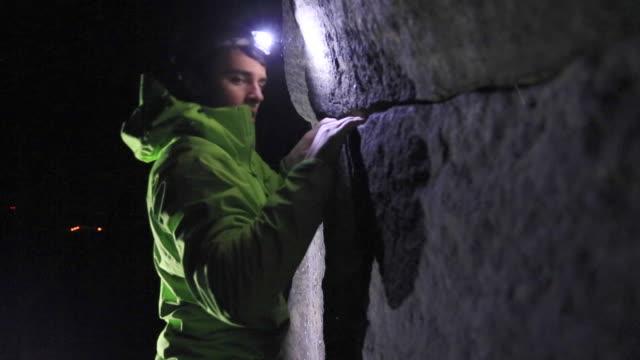 a young man climbs boulders at night while bouldering. - ヘッドライト点の映像素材/bロール
