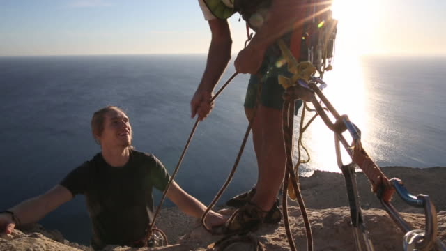 Young man climbs rock cliff to belayer, above sea