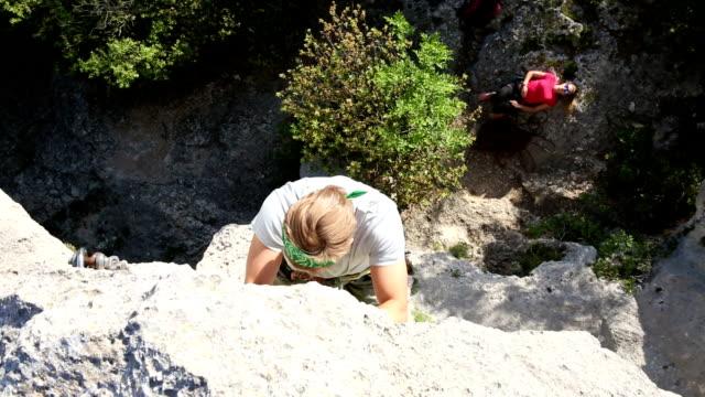 Young man climbs steep rock wall above belayer