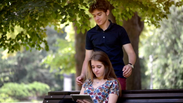 Young man close eyes his girlfriend while she surfs the net with a digital tablet