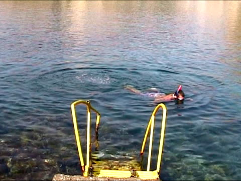 stockvideo's en b-roll-footage met young man comming out of the water after snorkeling - zwembroek
