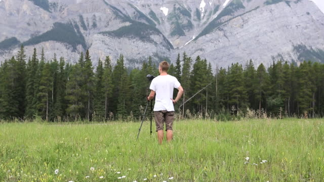 young man composes photo in mountain meadow, slr camera  - slr camera stock videos and b-roll footage