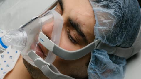 vídeos de stock e filmes b-roll de young man connected to a ventilator mask - equipamento respiratório