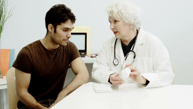 Young Man Consulting Female Doctor