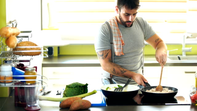 young man cooking at home. - cucina domestica video stock e b–roll