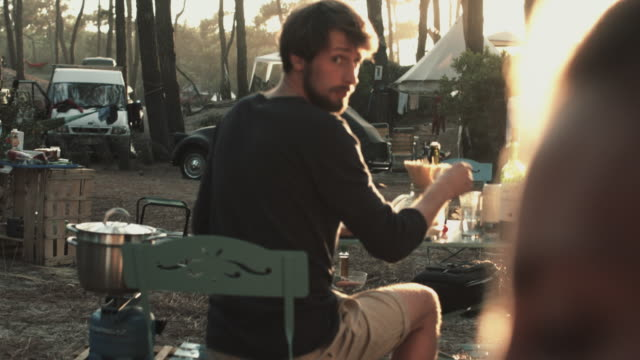 vidéos et rushes de young man cooking dinner at camping table in campground in the south of france. - camping