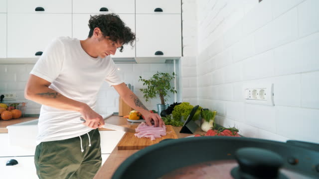 vídeos de stock, filmes e b-roll de jovem homem cozinhando na cozinha. - receita