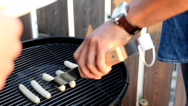 young man cooking sausages on barbecue grill - serving tongs stock videos & royalty-free footage