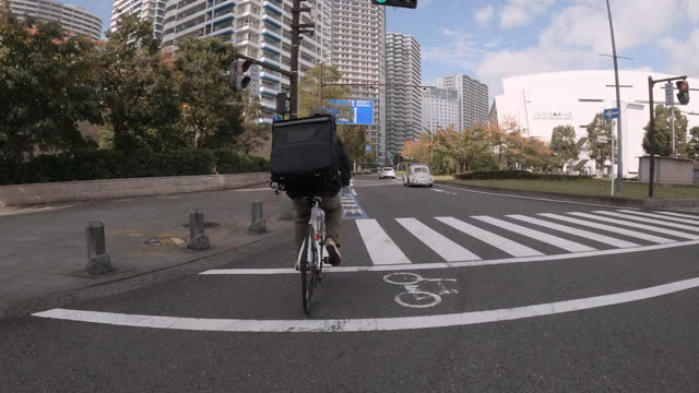 young man courier with black backpack and protective mask rides a bicycle on the street through the city with food delivery. video shot is from the back. crossing the road. food delivery concept. - plusphoto stock videos & royalty-free footage
