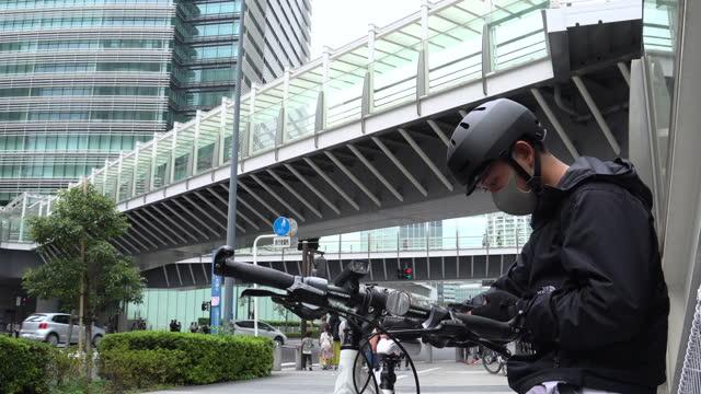 黒いバックパックを持つ若い男の宅配便は、彼の手に電話を保持し、周りを見回します。住所を探している自転車宅配便。高層ビルの真ん中に立つ。 - resting点の映像素材/bロール